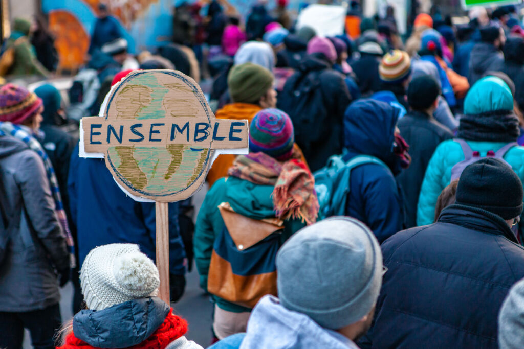 environmental activists march in city. a french sign is seen close up, depicting planet earth and saying together, during a street demonstration by eco activists, with copy space on the right