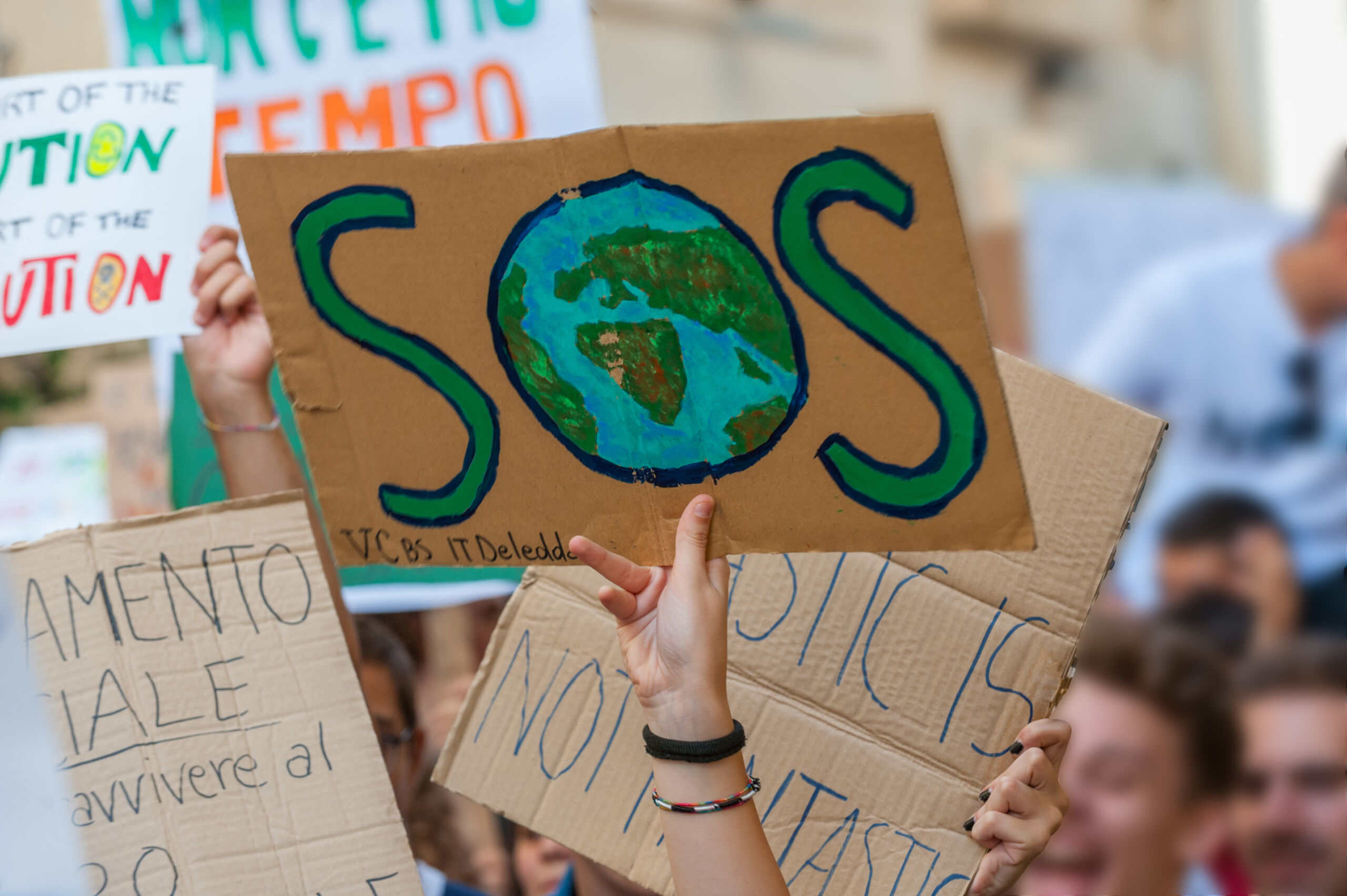 fridays for future: students hands showing banners and boards; sos