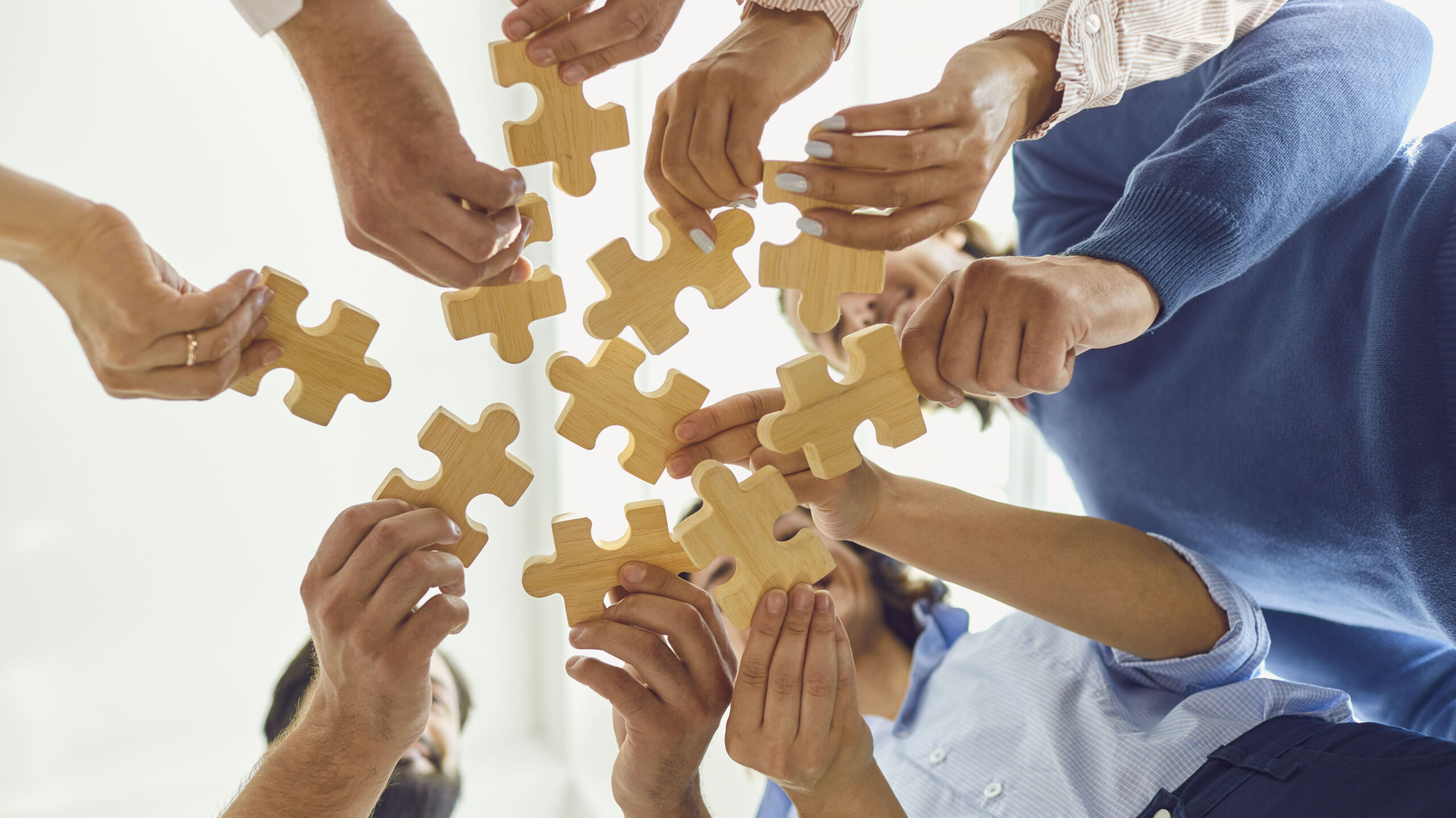 positive company workers playing with jigsaw puzzle during team building activity